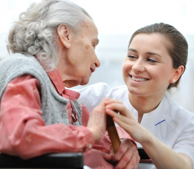 Senior woman with her caregiver at home - Caring Hearts Home Care
